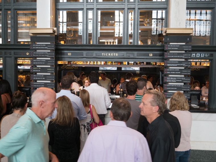 People standing in line to buy drinks at the old ticket window